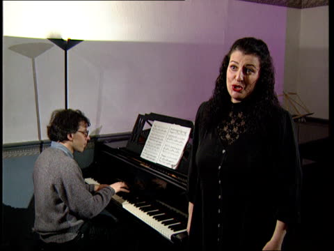 vocal cord instrument:; england: london: tms side pianist playing piano as rita halvani beside tcms fingers playing piano rita halvani singing sot as... - ガーゼ点の映像素材/bロール