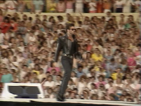 wham's last concert:; england: london: wembley stadium: ext mass screaming fans george michael lookalike in crowd fan taken away after fainting from... - crowd stock videos & royalty-free footage