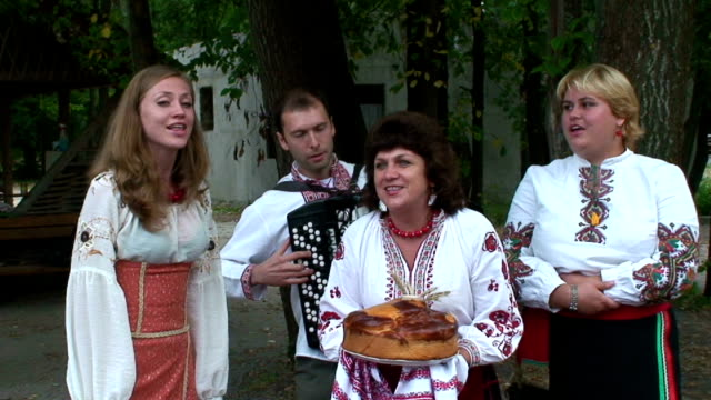 A musical group dressed in traditional costumes sing at a town fair in Sorochintsky Yarmarok Ukraine shot on August 20th 2011