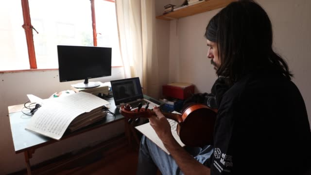 vídeos de stock e filmes b-roll de musician alexander bruck plays during a demonstration for his student as he gives a music lesson for the viola via an online streaming call during... - violino