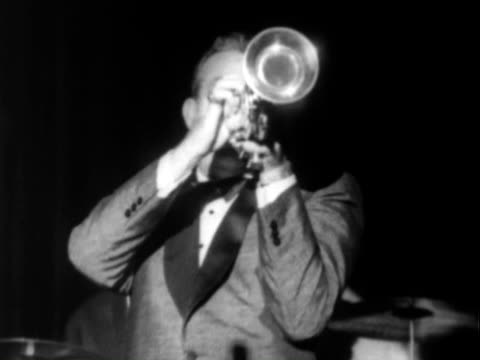 stockvideo's en b-roll-footage met musician bandleader harry james performing playing trumpet on stage / betty grable walking onto stage into spotlight wearing white evening gown /... - saxofonist