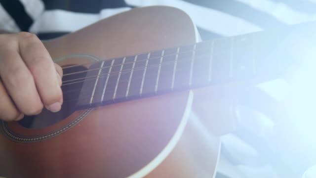 vidéos et rushes de musicien: main de gros plan règles du jeu de guitare à domicile - doigt humain