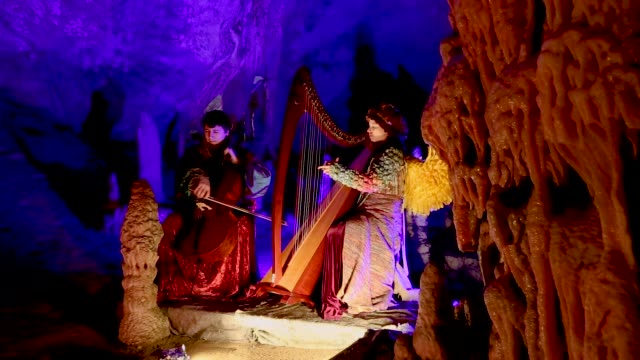 musician dressed as an angel performs during live biblical scene in postojna cave on december 25 2018 in postojna slovenia the annual nativity scene... - avvenimento biblico video stock e b–roll