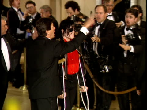 musician entertainer michael joseph jackson aka the king of pop wearing sunglasses walking w/ crutches on red carpet press taking photographs bg - 1993 stock videos & royalty-free footage