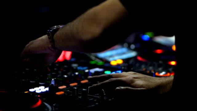 stockvideo's en b-roll-footage met muzikant handen mixen de track op dj stage in night club op disco party - club dj