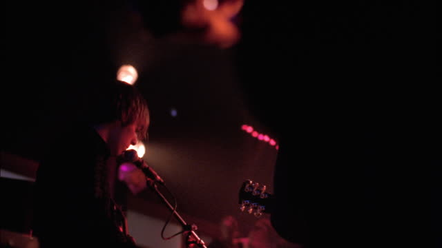 A musician in a rock band plays guitar and sings in a small, smoky club with flashing lights.