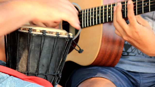 A musician mixed playing with drum and guitar