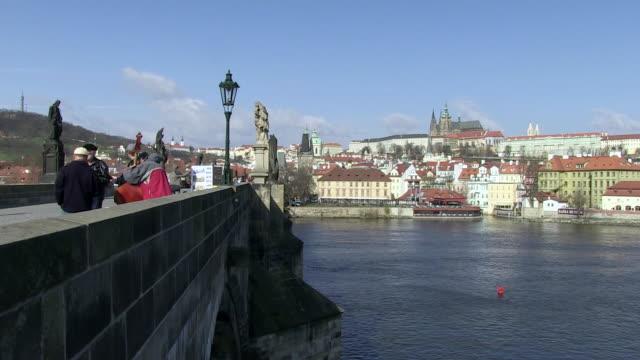 ms musician performing on bridge over vltava river with city  / prague, hlavni mesto praha, czech republic - river vltava stock videos & royalty-free footage