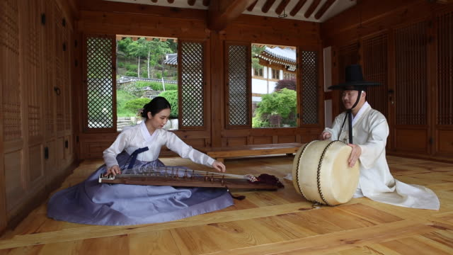 a musician playing a gayageum (korean zither with twelve strings) and a drummer playing a drum in korean-style house - performing arts event stock videos & royalty-free footage
