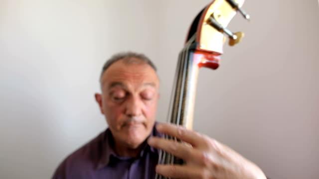 musiker spielen kontrabass neben dem fenster - jazz stock-videos und b-roll-filmmaterial
