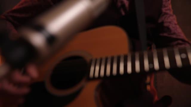 vídeos de stock, filmes e b-roll de músico que joga a guitarra no estúdio - violão acústico