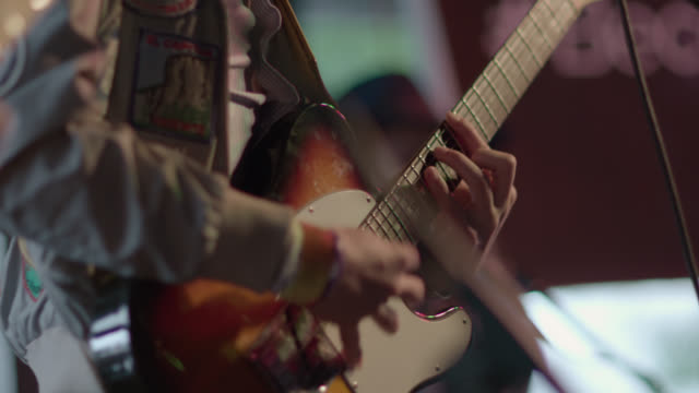 vídeos de stock e filmes b-roll de musician plays electric guitar on stage with band in austin bar - rocking