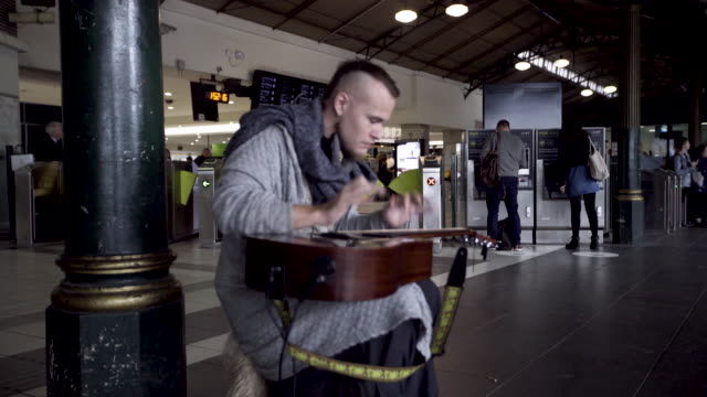 musician plays guitar in railway station - performer stock videos & royalty-free footage