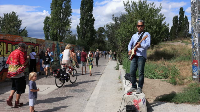 musician plays guitar while people enjoy the sunny and warm summer weather at mauerpark in the district prenzlauer berg during the coronavirus crisis... - plucking an instrument stock videos & royalty-free footage