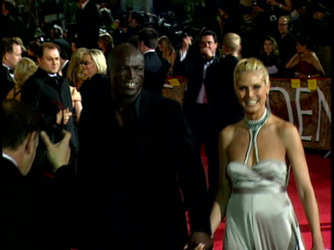 Musician Seal wife supermodel Heidi Klum walking down red carpet at Beverly Hilton hotel walking over to press reporters