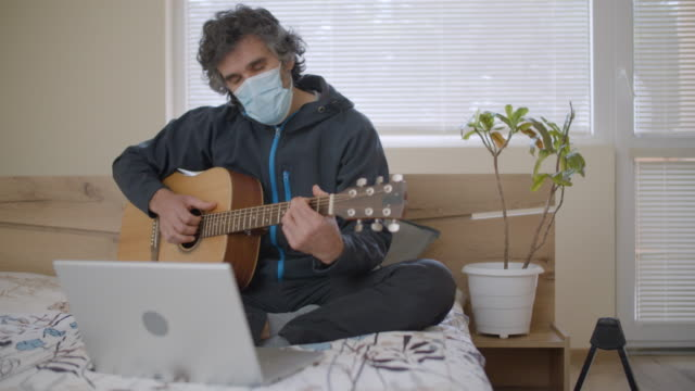 musician working from home during the covid-19 pandemic. freelancer working from his bedroom with his laptop and his guitar. active seniors young at heart. - zen like stock videos & royalty-free footage