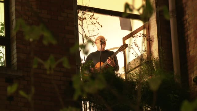musicians and singers living in a building in the barbes district of paris improvise a concert from their windows in homage to the medical staff on... - musicista video stock e b–roll