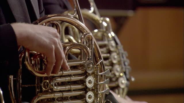 cu musicians holding french horns / london, united kingdom - 金管楽器点の映像素材/bロール
