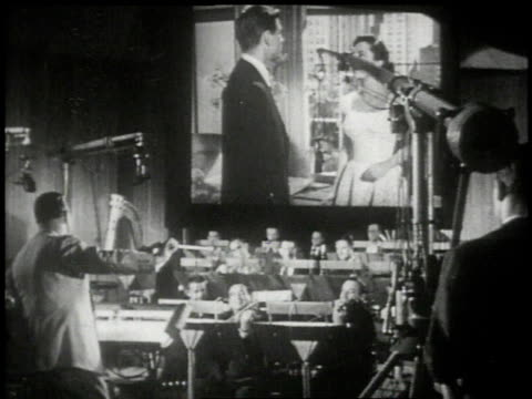 1951 montage musicians orchestrating background music for the film on the scoring stage  - film director video stock e b–roll