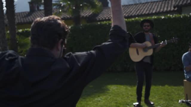 vídeos de stock e filmes b-roll de musicians perform music for friends in garden party, dancing - vídeo musical
