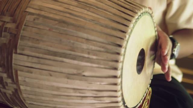 ミュージシャンがタイスタイルのドラムを演奏 - レゲエ点の映像素材/bロール