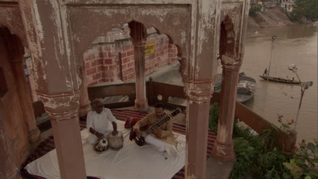 MS CS ZO Musicians playing sitar and tabla drums in  stone cuppola over Ganges river / India