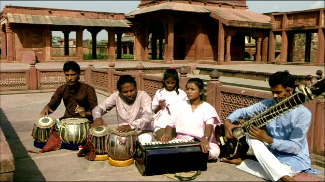 Musicians sit playing instruments at Agra Fort, Agra