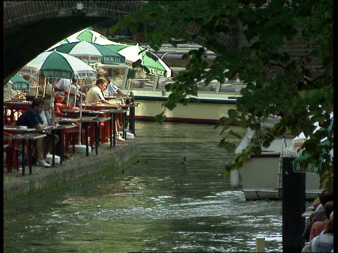muslem campaign against prostitution day utrecht lms river boat houses / tms canal in town centre / ms as people sitting at table and chair at canal... - utrecht stock videos and b-roll footage