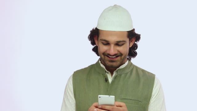 Muslim adult man chatting on a mobile phone and smiling