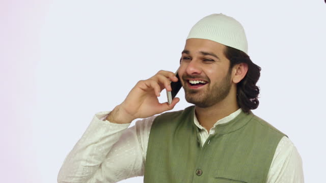 Muslim adult man talking on a mobile phone and smiling