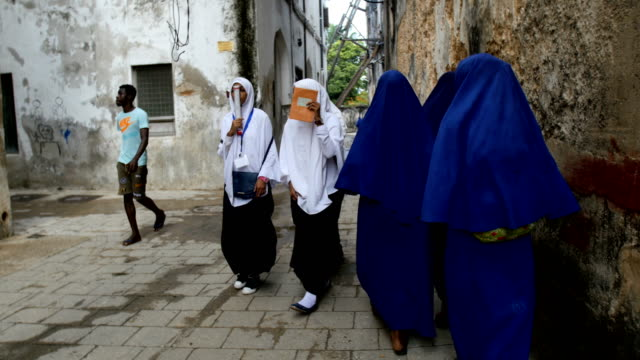 muslim african school children walking to school /over the shoulder, zanzibar - tanzania stock videos & royalty-free footage