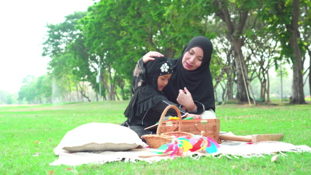 muslim asian mother and teenage daughter wearing religious dress having a picnic at a public park in weekend activities, daughter laying down, and playing wooden toys with mother. concept of the happiness muslim family. - religious dress stock videos & royalty-free footage