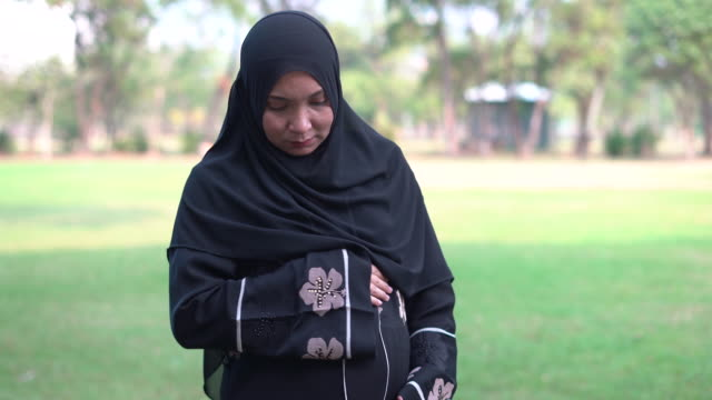 muslim asian pregnant wearing a religious dress called hijab with feeling love  to make positive emotion for the fetus, and touching belly on the carpet at public park - religious dress stock videos & royalty-free footage