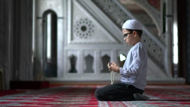 muslimische jungen beten in der moschee - schulkind nur jungen stock-videos und b-roll-filmmaterial