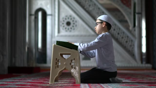 muslim boy reading the holy koran in mosque - koran stock videos and b-roll footage