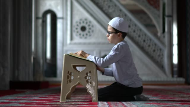 muslim boy reading the holy koran in mosque - one boy only stock videos & royalty-free footage