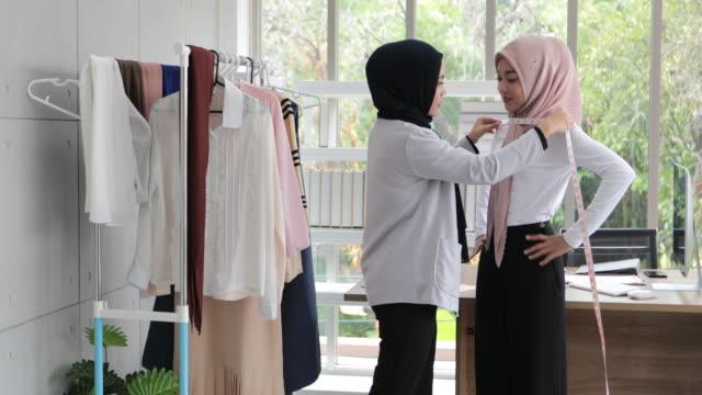 vidéos et rushes de femme d'affaires musulmane dans l'achat traditionnel de sac de fixation et de vêtement avec la carte de crédit - vêtement religieux