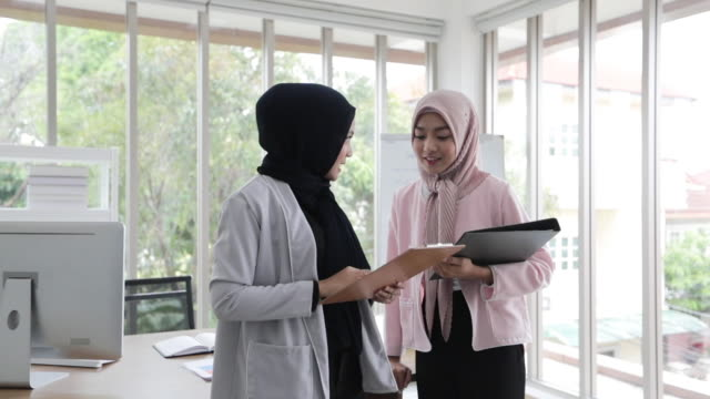 muslim business woman in traditional clothing shaking hands and smiling their agreement to sign contract and finishing up a meeting - employee engagement stock videos & royalty-free footage
