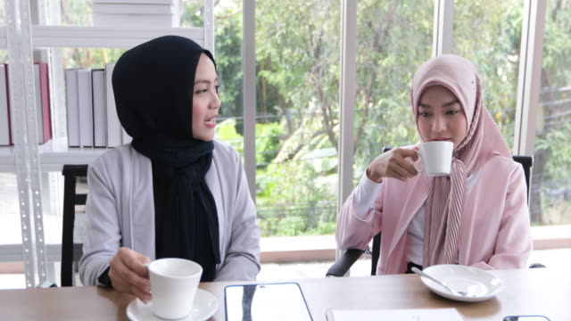 vídeos de stock e filmes b-roll de muslim business woman in traditional clothing working and discussing at meeting and drinking coffee in office - outro tema