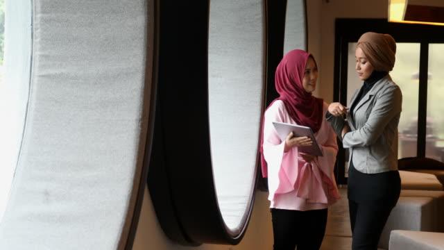 vídeos de stock, filmes e b-roll de mulheres de negócios muçulmano tendo uma reunião em um escritório moderno - vestuário modesto