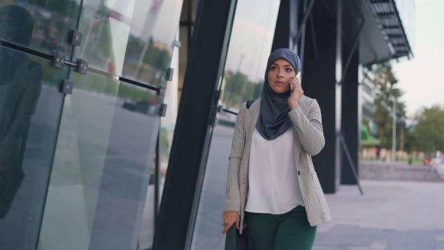 vidéos et rushes de femme d'affaires musulmane a un appel téléphonique - hijab