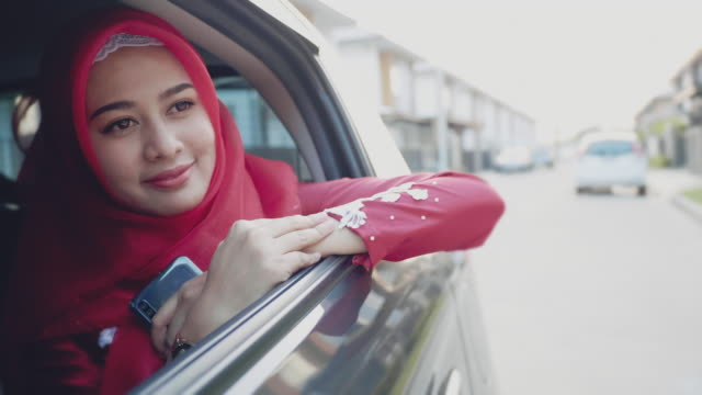 a muslim businesswoman sitting on back seat of a car and looking outside the window. female business executive travelling by a cab. - urban road stock videos & royalty-free footage