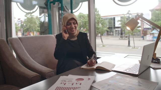 Muslim businesswoman talking on phone in cafe