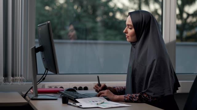 オフィスで働くイスラム教徒のビジネスウーマン - 製図板点の映像素材/bロール