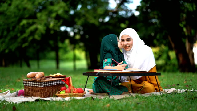 muslim daughter kissing her mother during a picnic at the park - meal stock videos & royalty-free footage