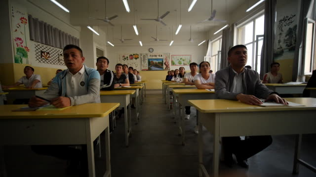 muslim ethinc groups learning chinese by rote at secure reeducation facility in xinjiang promoted by china as a school to combat islamist extremism - prison education stock videos & royalty-free footage