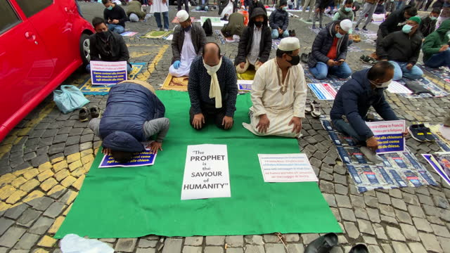 vídeos de stock, filmes e b-roll de muslim faithful attend prayer organized by the muslim community in the city centre near the french embassy to protest against the cartoons of the... - sátira