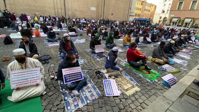vídeos de stock, filmes e b-roll de muslim faithful hold placards during prayer organised by the muslim community in the city centre near the french embassy to protest against the... - sátira