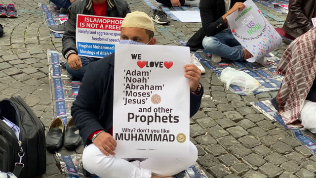 vídeos y material grabado en eventos de stock de muslim faithful hold placards during prayer organised by the muslim community in the city centre near the french embassy to protest against the... - satírico