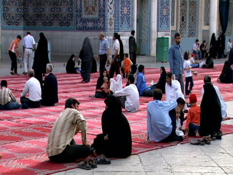 vidéos et rushes de muslim families gathering in qom shrine as an elder sings an arabic song of prayer / qom, iran - format vignette